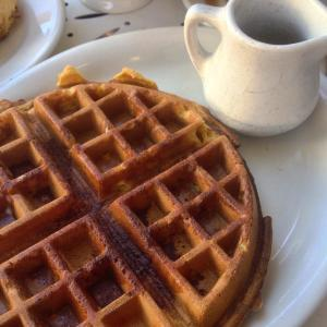 Pumpkin waffle with cinnamon, and maple syrup on the side