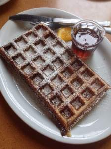 Waffle with powdered sugar and a side of maple syrup