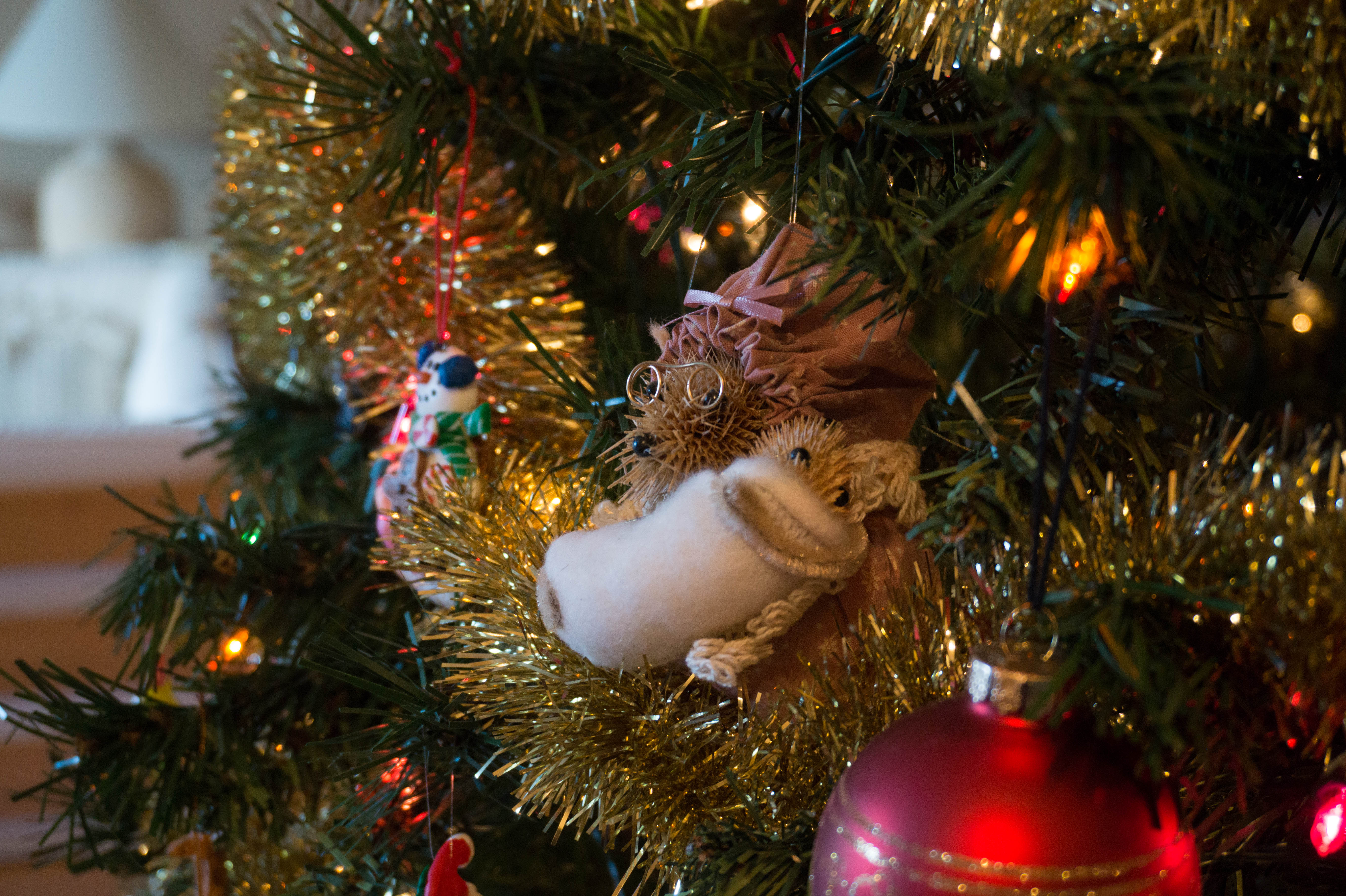 Ornament of mother mouse holding baby hanging on Christmas tree.